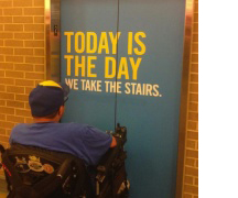 Man in wheelchair in front of elevator with sign that says 'Today Is the Day we take the stairs