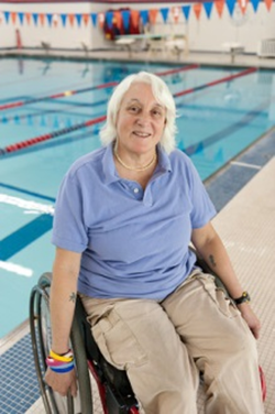 Image of Bo Tanner in her wheelchair in front of pool where she coaches