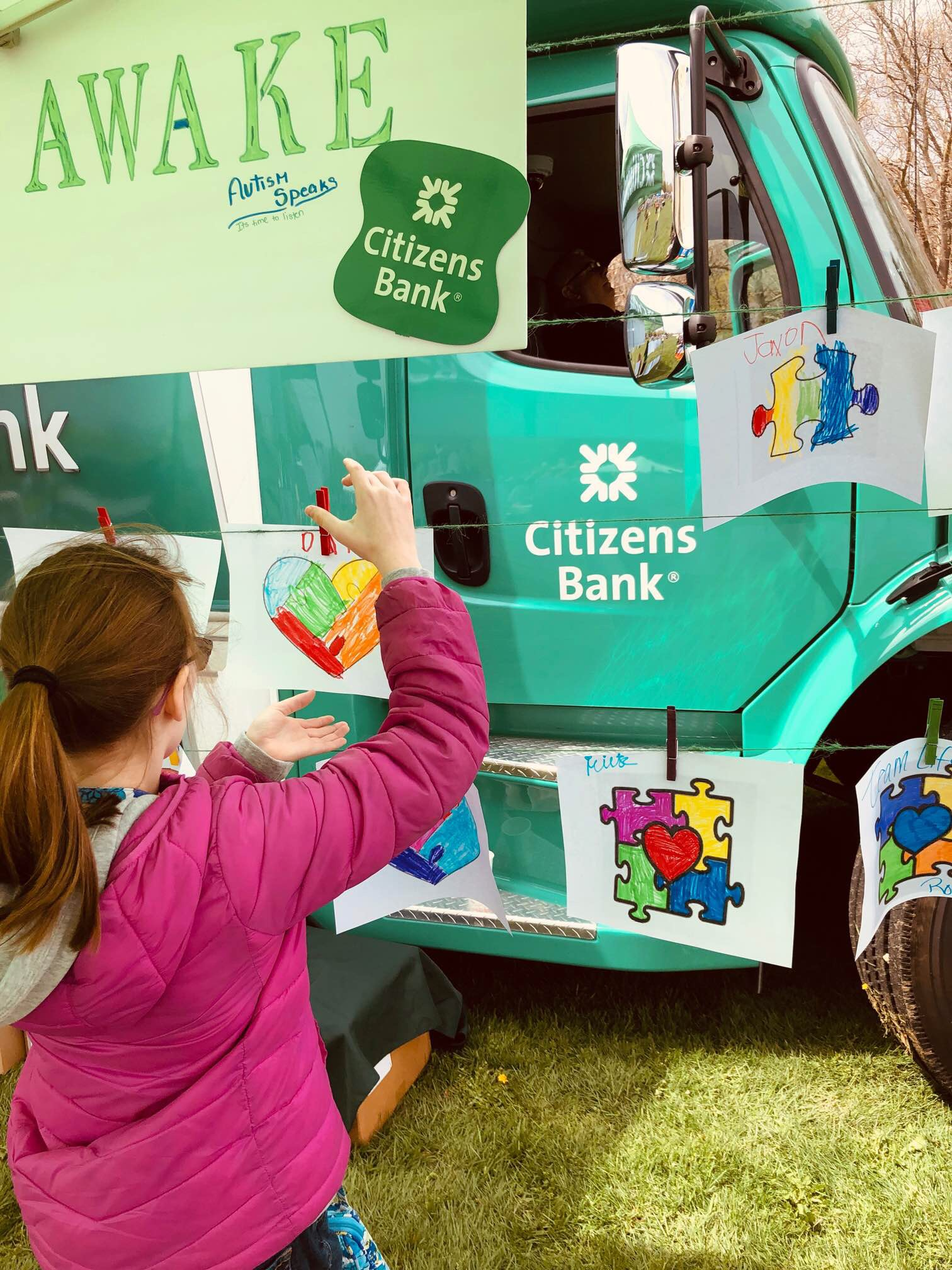 Woman at citizens truck with autism puzzle logo